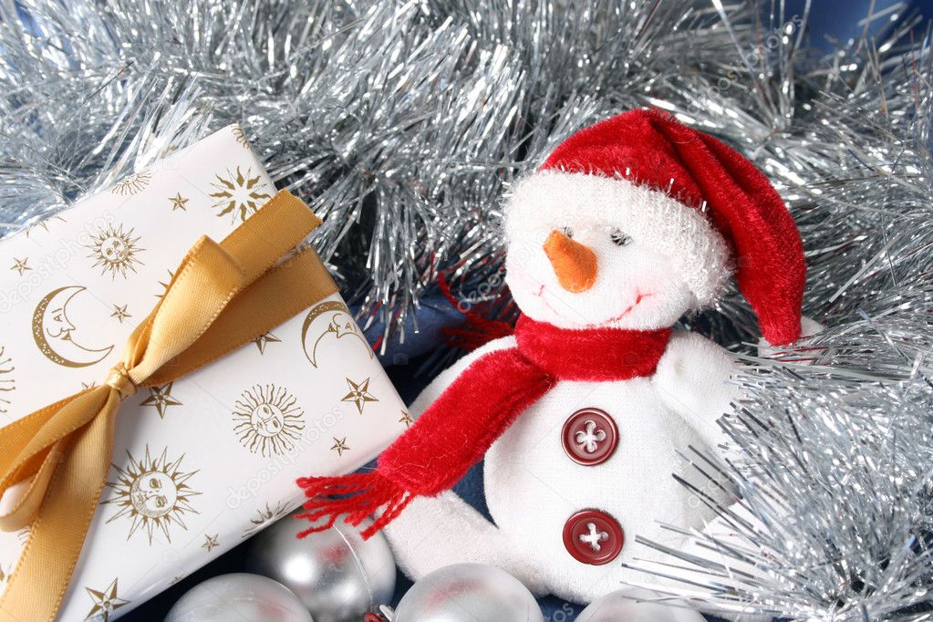 Wrapped christmas gifts with tinsel and snowman decoration — Zdjęcie stockowe #9269074