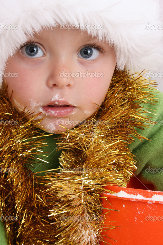 Toddler wearing a christmas hat, baking christmas cookies — Stock Photo #9660338