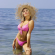 Sexy blonde in a bikini and straw hat. — Stock Photo