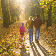 Young family walking in the autumn park — Stock Photo #8085264
