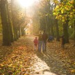 Young family walking in the autumn park — Foto Stock
