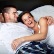 Happy young couple in bed — Stockfoto