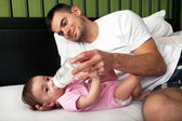 Portrait of father feeding daughter — Stock Photo