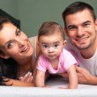 Mother, father and baby on the white bed - Stock Photo