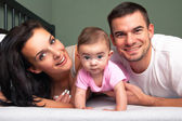 Mother, father and baby on the white bed — Stock Photo