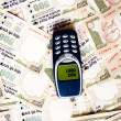 Mobile phone on Indian currency — Stock Photo