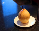 Saucer with a pear — Stock Photo