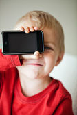 Small boy and media player — Stockfoto