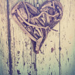 Driftwood heart on vintage wall — Stock Photo #9935823