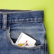 Playing card in blue jeans pocket — Stock Photo