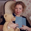Girl with book and teddy — Stock Photo