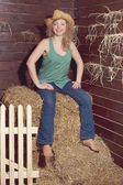 Blonde girl portrait in cowboy hat on straw bales background. — Stock Photo