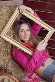 Beautiful girl in hay with a frame — Stock Photo