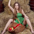 Beautiful girl on hay with basket of apples — Stock Photo
