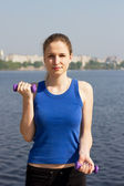 Young woman with weights exercising in the nature — Stock Photo