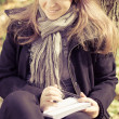 A girl writes on a pad in the park — ストック写真