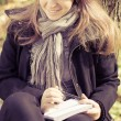 A girl writes on a pad in the park — Stockfoto