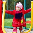 Stock Photo: Little girl in winter clothing deals on fitness equipment outdoor