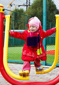 The little girl in winter clothing deals on fitness equipment outdoor — Stock Photo
