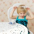 The little girl in a dress sitting on a chair — Stock Photo
