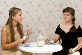 Two girls talking at a table in a cafe — Stock Photo