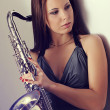 Girl and a saxophone — Stock Photo