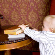 Boy runs to the books lying on a table — Stock Photo