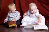 Children read books sitting on the floor against — Stock Photo
