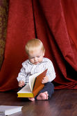Boy reading a book sitting on the floor against — Stock Photo