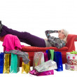 Tired woman lying on a red couch, around the shopping bags in pa — Stock Photo