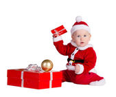 Little baby boy wearing Santa's costume sitting and holding a box with — Stock Photo