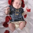 A well-dressed baby with an entourage of red petals — Stock Photo #8061577