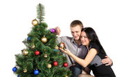Family man and a woman, dress up a Christmas tree — Stok fotoğraf