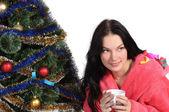 Hermosa chica con una copa en bata de baño junto al árbol de navidad — Foto de Stock