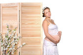 Pretty pregnant woman with flowers — Stock Photo