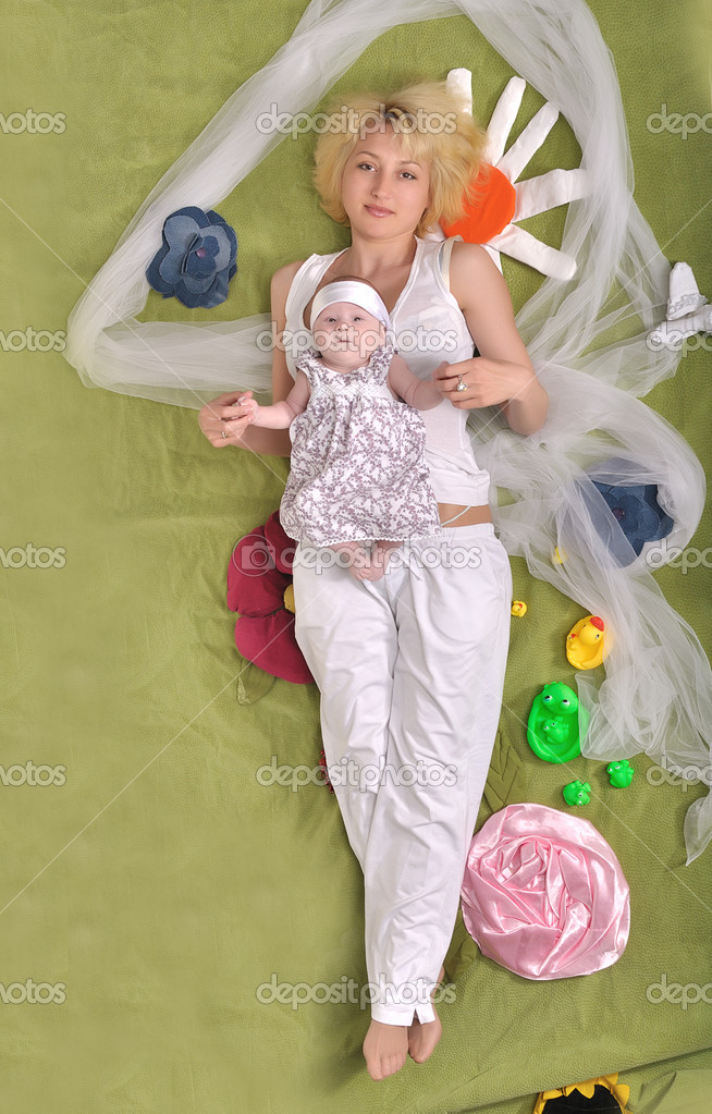 A young mother and her little daughter lie full-length on developmental mat — Stock Photo #8061578