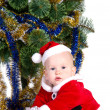 Little baby boy wearing Santa's costume sitting and holding a box with — Stock Photo #8085088