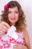 Beautiful pregnant girl in pink dress holding baby socks 1 — Stock Photo