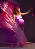 Beautiful pregnant woman in pink and violet dress 2 — Stock Photo