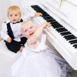 Royalty-Free Stock Photo: Boy and girl playing on a white piano