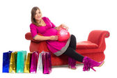 Pregnant women in pink color dresses, with shopping bags — Stock Photo