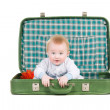 Baby sitting in an old green suitcase in anticipation of traveli — Stock Photo #9770364