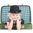 图库照片: Child sitting in old green suitcase in anticipation of travel