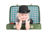 Child sitting in an old green suitcase in anticipation of travel — Stock Photo