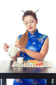 Girl pouring tea and eating sushi — Stock Photo