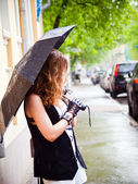 Girl with umbrella in the rain is on the street — Stock Photo