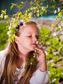 The girl inhales the fragrance of a flowering tree in spring — Stock Photo