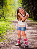 The little girl in rubber boots standing in a summer park — Stock Photo