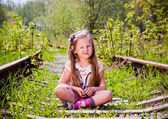 The little girl in rubber boots sitting on an old railroad — Stock Photo
