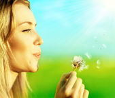 Happy beautiful girl blowing dandelion — Stockfoto